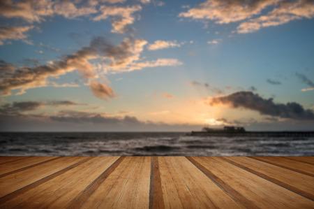 Beautiful Winter sunset sky over long exposure waves in ocean with wooden planks floor