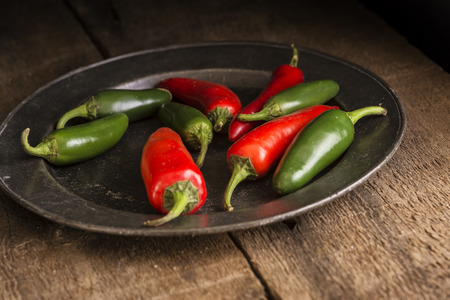 Red and green peppers in vintage moody natural lighting setting