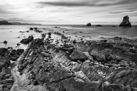 mupe bay: Black and white landscape of Mupe Bay with rocks in foreground