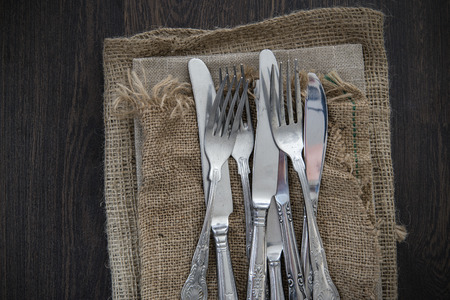 vintage cutlery: Vintage cutlery on hessian cloths on wooden background