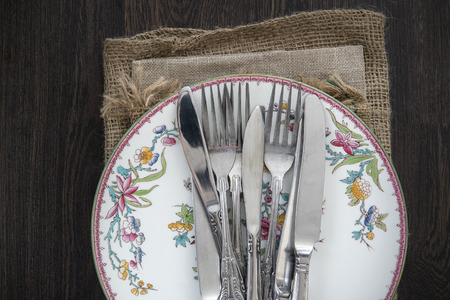 vintage cutlery: Vintage cutlery and crockery on cloths in rustic setting