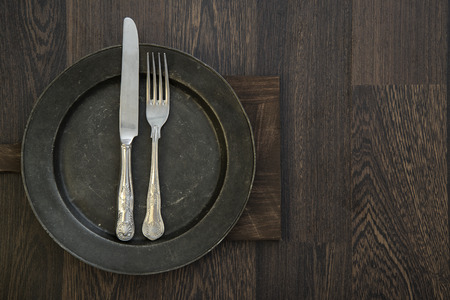 Pewter plate and vintage cutlery on rustic wooden background