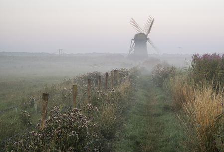 english countryside: Old windmill in foggy English countryside landscape