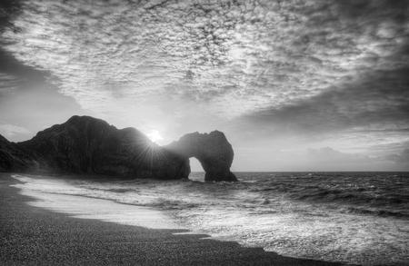 jurassic coast: Winter sunrise behind Durdle Door on Jurassic Coast in black and white