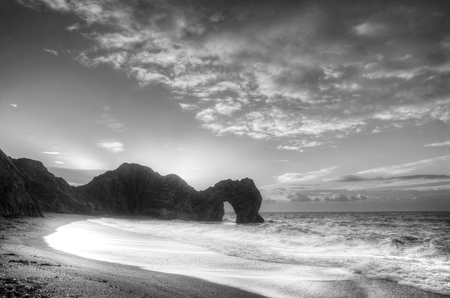 jurassic coast: Winter sunrise over Durdle Door on Jurassic Coast in black and white