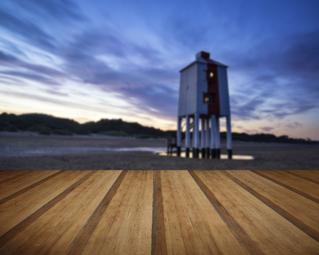 Stunning landscape sunrise stilt lighthouse on beach with wooden planks floor