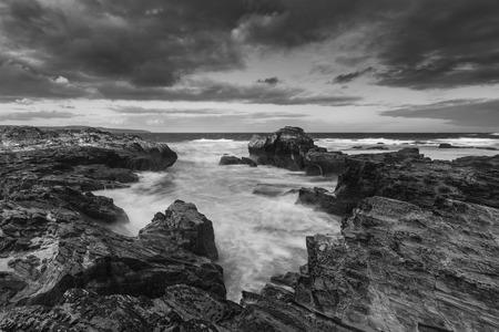 pano: Stunning sunrise landscape of Godrevy on Cornwall coastline in England black and white