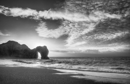 durdle door: Winter sunrise behind Durdle Door on Jurassic Coast in black and white
