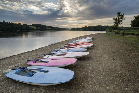 windsurfers: Summer sunset over lake in landscape with leisure boats on shore
