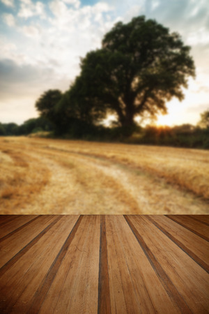 hay bales: Beautiful Summer sunset over field of hay bales in countryside landscape with wooden planks floor Stock Photo