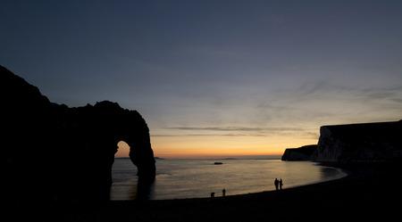 durdle door: Stunning sunset silhouette landscape image of Durdle Door in England