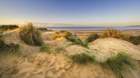sand dunes: Stunning sunrise over sand dunes system on yellow sand golden beach Stock Photo