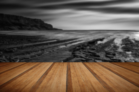 Stunning black and white seascape coastline and rocky shore at sunset with wooden planks floor Stock Photo