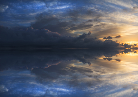 reflected: Large panorama image of stormy sunset sky reflected in still water Stock Photo