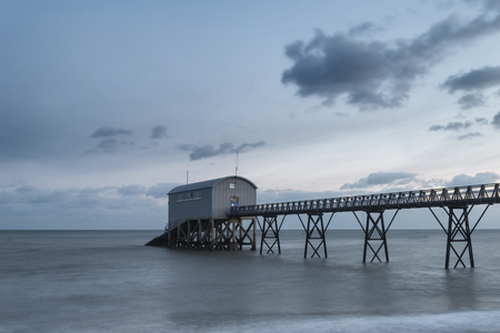Beautiful long exposure landscape image of lifeboat jetty at sea