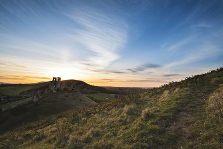 Landschap foto van betoverende sprookjesachtige kasteelruïne tijdens de prachtige zonsondergang