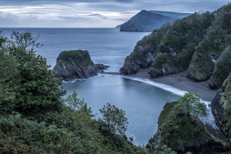 secluded: Beautiful moody sunrise landsape image of small secluded cove at Combe Martin Bay