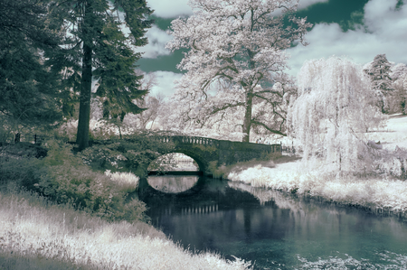 Stunning infra red landscape image of old bridge over river in countryside Stock Photo