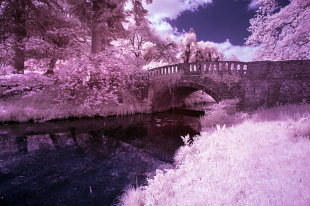 specialised: Stunning infra red landscape image of old bridge over river in countryside Stock Photo