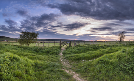 Stunning English countryside panorama landscape over fields at sunset
