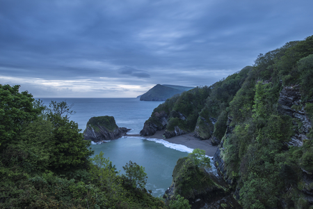 Beautiful moody sunrise landsape image of small secluded cove at Combe Martin Bay