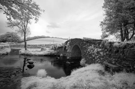 infra red: Stunning black and white infra red landscape image of old bridge over stream