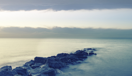 of pano: Peaceful cross processed landscape image of calm sea over rocks at sunrise Stock Photo