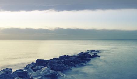 serene landscape: Peaceful cross processed landscape image of calm sea over rocks at sunrise Stock Photo