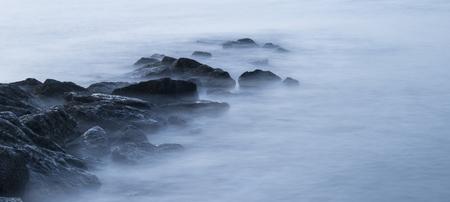 cross processed: Peaceful cross processed landscape image of calm sea over rocks at sunrise Stock Photo