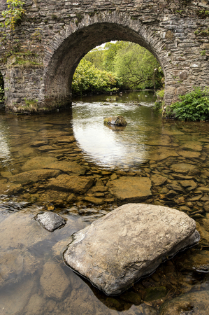 Landscape image of old medieval bridge in river setting in English countryside