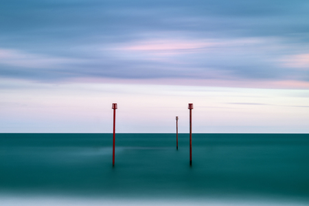 Beautiful vibrant conceptual image of posts in sea standing sentinel against the weatherand tide