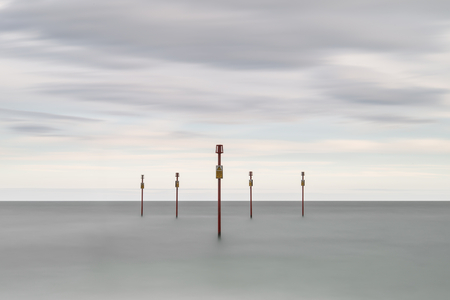 the sentinel: Beautiful vibrant conceptual image of posts in sea standing sentinel against the weatherand tide