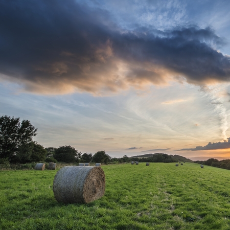 hay bales: Beautiful Summer sunset over countryside landscape of field with hay bales