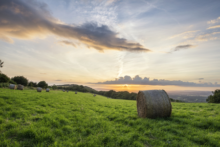 Beautiful Summer sunset over countryside landscape of field with hay bales