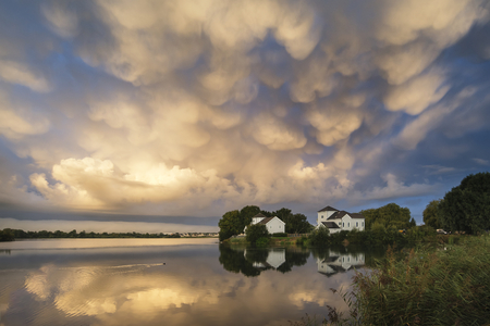 Stunning mammatus clouds formation over lake landscape immediately prior to violent storm