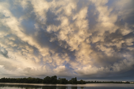 prior lake: Stunning mammatus clouds formation over lake landscape immediately prior to violent storm