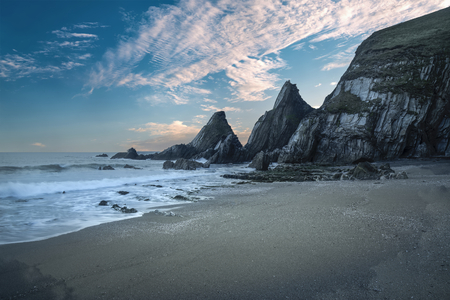 Beautiful colorful sunset over beach landscape with jagged rock formations