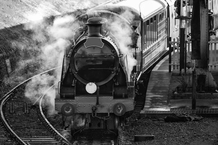 historic vintage: Historic vintage steam railway engine in station with full steam puffing in black and white Stock Photo
