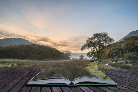 cumbria: Beautiful foggy misty Fall sunrise over countryside surrounding Crummock Water in Lake District in England coming out of pages of book Stock Photo
