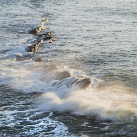 Wave crashing over rocks in ocean at sunrise Stock Photo