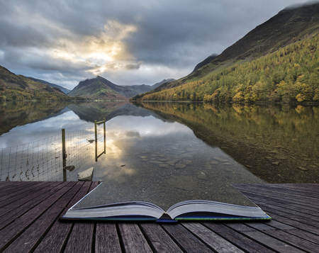 cumbria: Stunning Autumn Fall landscape image of Lake Buttermere in Lake District England coming out of pages of book Stock Photo
