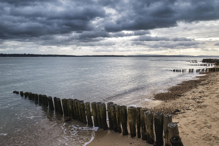 Beautiful sea landscape looking across Solent to Isle of Wight in England with moody dramatic sunset sky