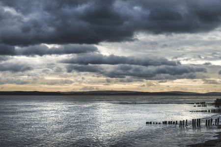 groynes: Beautiful sea landscape looking across Solent to Isle of Wight in England with moody dramatic sunset sky