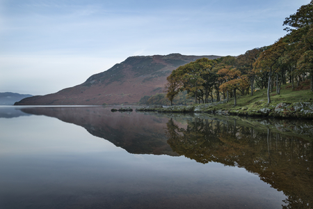 Stunning Autumn Fall landscape image of Crummock Water at sunrise in Lake District England Stock Photo