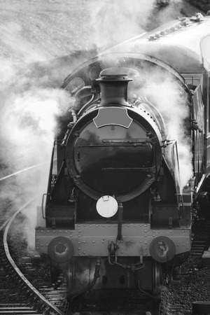 industrialised: Victorian era steam train engine with full steam in black and white