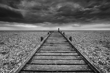 Conceptual image of path to nowhere in black and white beach landscape