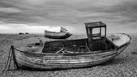 Abandoned derelict fishing boats on shingle beach landscape in Winter