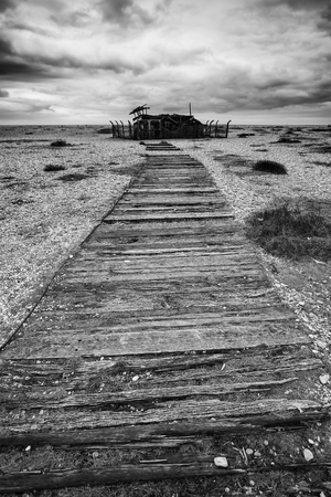 overcast: Conceptual image of path to nowhere in black and white beach landscape