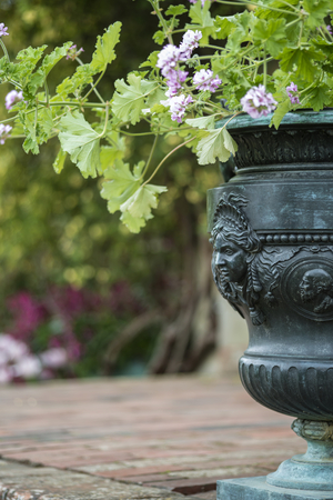 Beautiful shallow depth of field image of English country garden with urn style planter with flowers