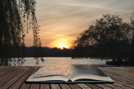 fictional: Beautiful Spring sunrise over calm lake in English countryside concept coming out of pages in open book